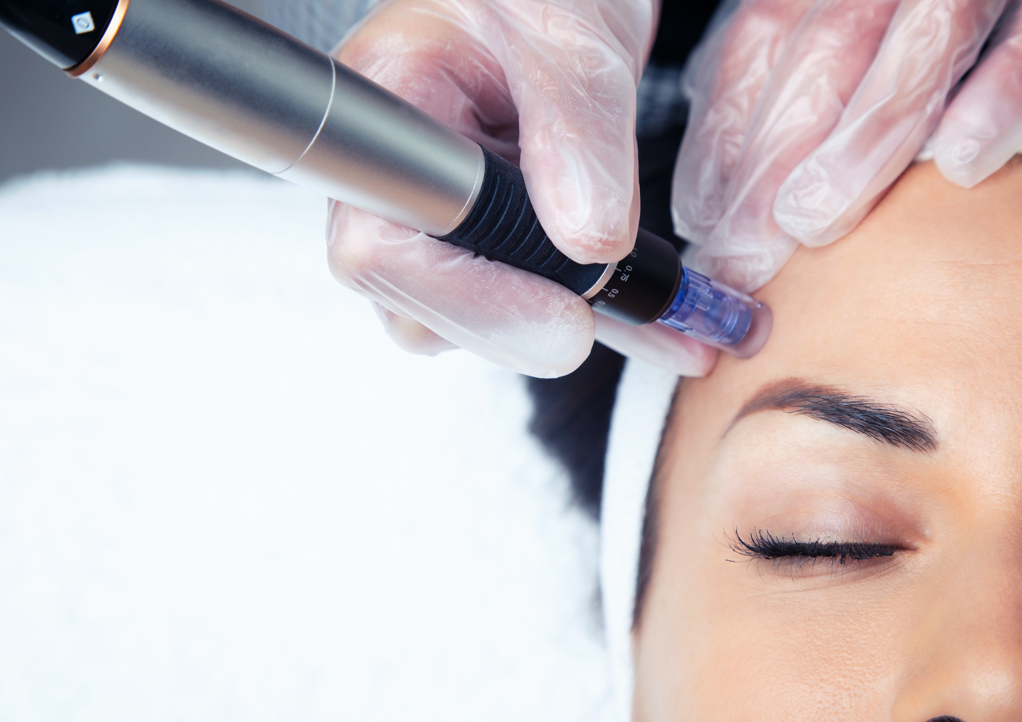 Cosmetologist making mesotherapy injection with dermapen on face for rejuvenation on the spa center.